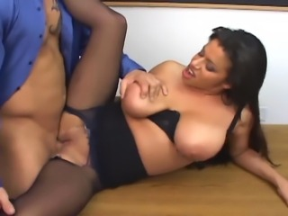 Busty MILF on a desk fucking in black ripped up crotchless pantyhose