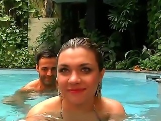 The seductive and very sympathetic pornstar Fernandinha swims in a pool with...