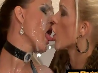 Two sluts jerking and sucking a black cock at the gloryhole