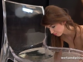 Dirty-minded girl Susan Ayn licks the urine off the transparent chair