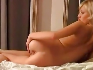 Cute shorthaired blonde Anna plays on the bed