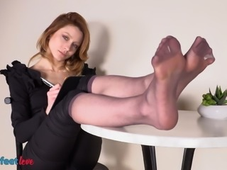 Business lady in nylons plays with her shoes