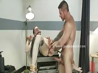 Strong hunk tied near cage gets spanking training from fetish officer and his...