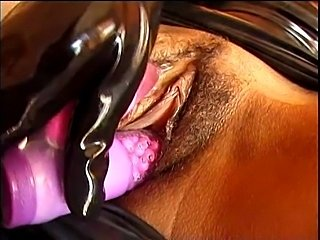 Kinky ebony in latex plays with some big toys